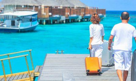 que llevar en la maleta al Caribe: viajeros con sus maletas de vacaciones en playas paradisiacas